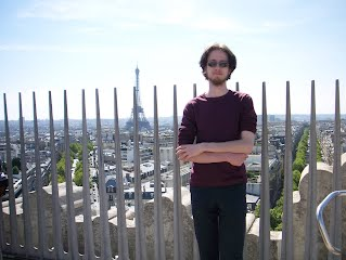 Standing on top of the Arc de Triomphe with the Eiffel Tower in the background.